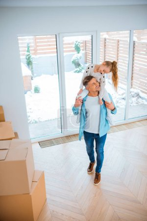 Photo pour Fille souriante regardant joyeux père exerçant son cou tout en marchant dans la nouvelle maison - image libre de droit