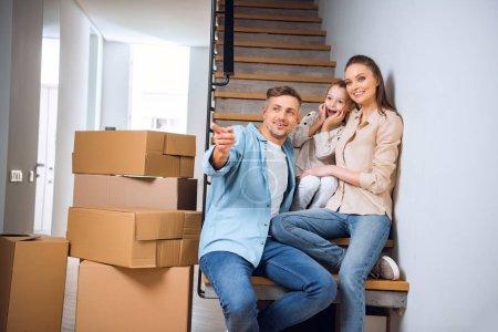 Photo pour Mari joyeux pointant du doigt et souriant tout en étant assis sur les escaliers près de la femme et de la fille dans une nouvelle maison - image libre de droit