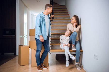 Photo for Handsome man looking at daughter and wife sitting on stairs in new home - Royalty Free Image