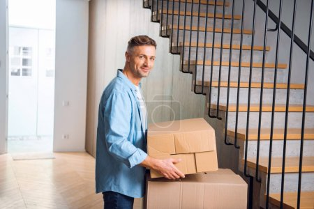 Photo for Handsome man holding box in hands and smiling near stairs in new home - Royalty Free Image