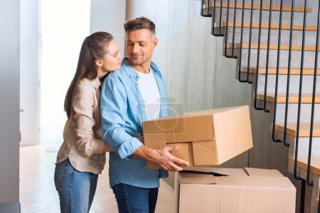 Photo for Attractive woman hugging handsome husband with box in hands in new home - Royalty Free Image
