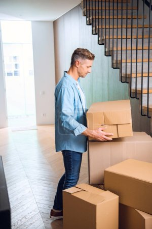Photo for Handsome man looking at box in hands while standing near stairs in new home - Royalty Free Image