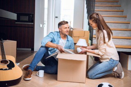 Photo for Cheerful husband looking at wife unpacking box and holding lamp in hands while sitting on floor - Royalty Free Image