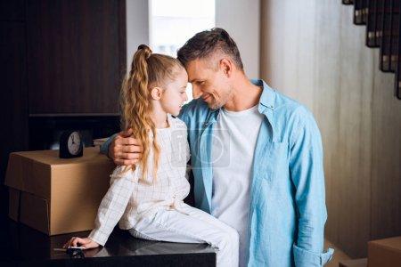 Photo pour Père heureux hugging fille et souriant dans la nouvelle maison - image libre de droit