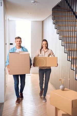 Photo for Happy couple walking with boxes and smiling in new home - Royalty Free Image
