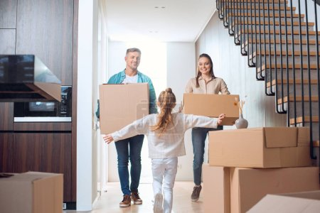 Photo for Selective focus of running kid looking at happy parents holding boxes in new home - Royalty Free Image