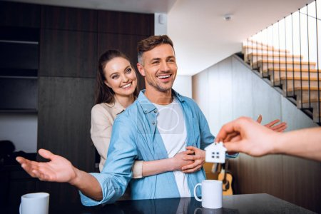 Photo for Cropped view of man giving house shaped key chain to cheerful couple in new home - Royalty Free Image