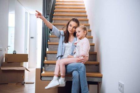 Photo pour Jolie femme siégeant avec jolie fille dans les escaliers et pointer avec le doigt dans la nouvelle maison - image libre de droit