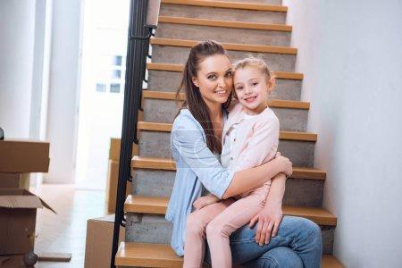 Photo pour Femme joyeuse assis avec fille dans les escaliers dans la nouvelle maison - image libre de droit