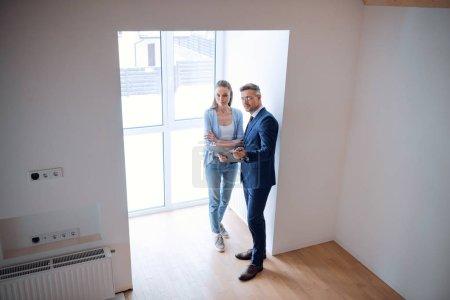 Foto de Broker guapo sosteniendo portapapeles y permanente con hermosa mujer en la habitación - Imagen libre de derechos