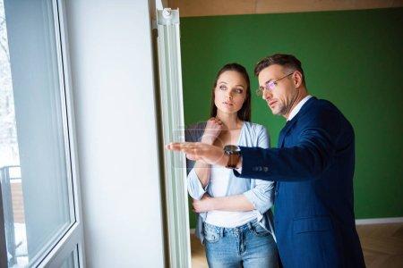 Foto de Hermoso corredor en gafas mostrando algo a mujer hermosa en nueva casa - Imagen libre de derechos