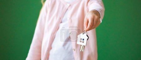 Foto de Vista recortada de cabrito con llavero de la casa en forma aislada en verde - Imagen libre de derechos