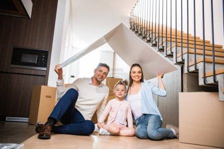 glückliche Familie sitzt unter Papierdach und lächelt im neuen Zuhause