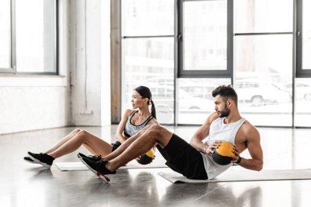 Photo pour Vue latérale de l'athlétique jeune couple sportswear tenant des ballons et exercice sur tapis d'yoga dans une salle de sport - image libre de droit