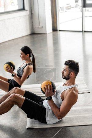 Photo pour Vue d'angle élevé d'athlétique jeune couple tenant des ballons et faire abs exercice sur tapis d'yoga - image libre de droit