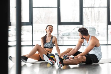 cheerful sporty young couple sitting on yoga mats with medicine balls and smiling each other in gym