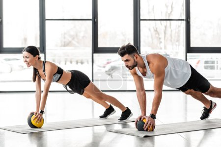 Photo for Athletic young couple in sportswear exercising with medicine balls on yoga mats and looking away in gym - Royalty Free Image