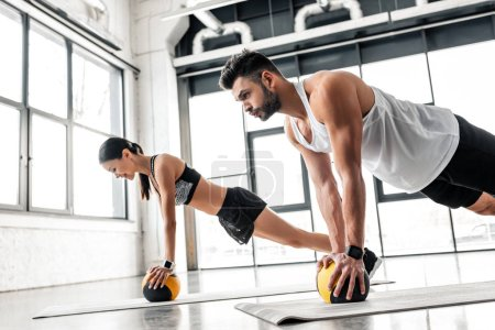 Photo for Side view of athletic young couple in sportswear exercising with medicine balls on yoga mats in gym - Royalty Free Image
