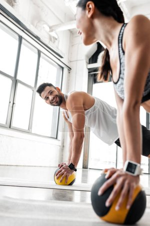 Photo for Athletic young couple smiling each other while exercising with medicine balls on yoga mats in gym - Royalty Free Image
