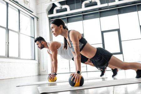 Photo pour Vue latérale du jeune couple sportive avec ballons sur tapis d'yoga - image libre de droit