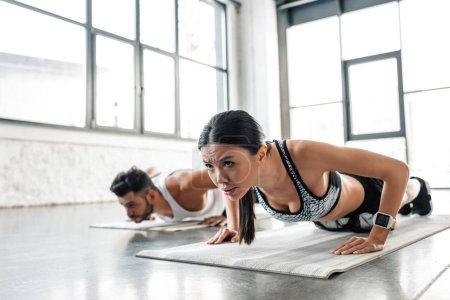 Photo pour Athlétique concentré jeune femme et homme faisant push ups sur tapis de yoga dans la salle de gym - image libre de droit