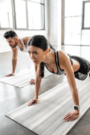 concentrated young woman and man doing push ups on yoga mats in gym