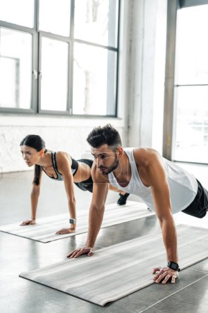 Photo for Athletic young man and woman in sportswear doing push ups on yoga mats in gym - Royalty Free Image