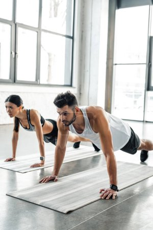 Photo for Athletic young couple in sportswear doing push ups on yoga mats in gym - Royalty Free Image