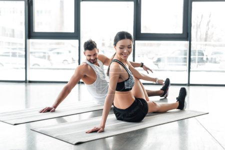 Photo for Happy young couple sitting on yoga mats and stretching in gym - Royalty Free Image