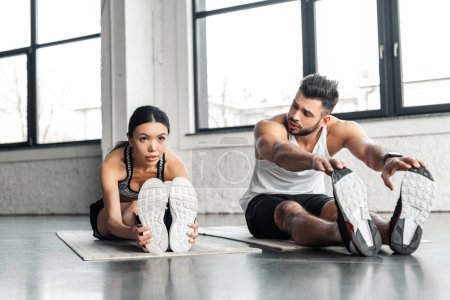 athletic young couple stretching legs and exercising on yoga mats in gym