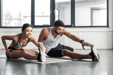 athletic young man and woman stretching legs on yoga mats in gym