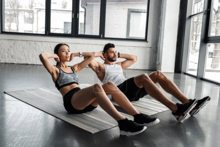 Photo for Athletic young couple doing abs exercise on yoga mats in gym - Royalty Free Image