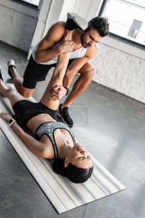 Photo for High angle view of male trainer helping young sportswoman stretching on yoga mat in gym - Royalty Free Image