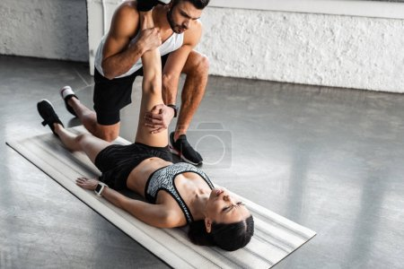 Photo for Athletic young man helping sporty woman stretching on yoga mat in gym - Royalty Free Image