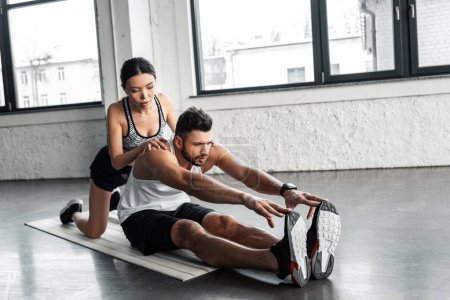 beautiful female trainer helping young sportsman stretching on yoga mat in gym
