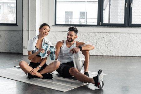 Photo pour Souriante jeune couple sportswear assis sur des tapis d'yoga et la tenue des bouteilles d'eau après la séance d'entraînement en gymnase - image libre de droit