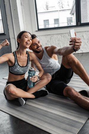 Photo pour Heureux jeune couple sportif prenant selfie avec smartphone tout en se reposant sur des tapis de yoga après l'entraînement dans la salle de gym - image libre de droit