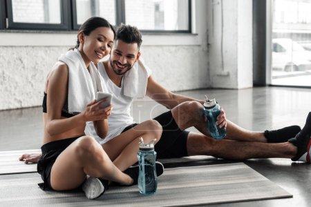 Foto de Joven deportivo feliz pareja descansando sobre esteras de la yoga y utilizando smartphone juntos en el gimnasio - Imagen libre de derechos