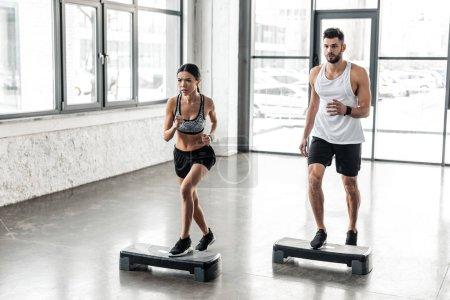 Photo for Muscular young man and beautiful sporty girl exercising together on step platforms in gym - Royalty Free Image