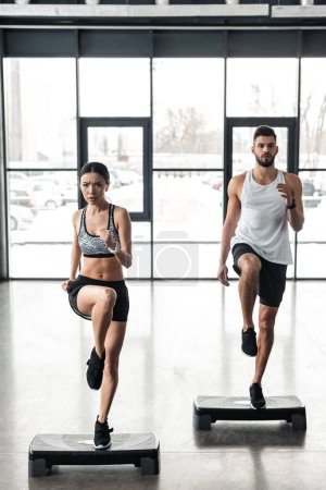 Photo for Full length view of athletic young couple training on step platforms in gym - Royalty Free Image