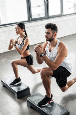 Photo for High angle view of concentrated young couple exercising on step platforms and looking away in gym - Royalty Free Image