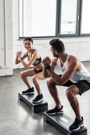 Photo for Young man and woman in sportswear smiling each other while training with step platforms in gym - Royalty Free Image