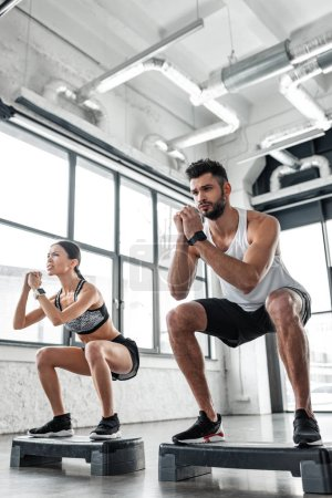 Photo for Low angle view of athletic young couple in sportswear training with step platforms in gym - Royalty Free Image