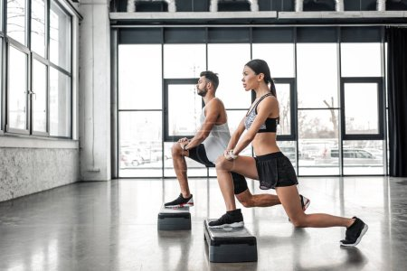 Photo for Side view of sportive young man and woman training with step platforms in gym - Royalty Free Image