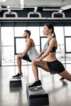 Photo for Side view of athletic young man and woman training with step platforms in gym - Royalty Free Image