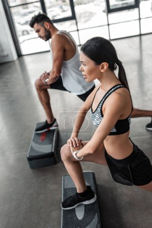Photo for High angle view of athletic young man and woman training with step platforms in gym - Royalty Free Image