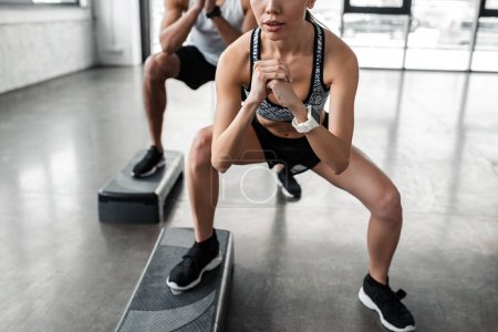 Photo for Cropped shot of athletic young man and woman in sportswear training with step platforms in gym - Royalty Free Image