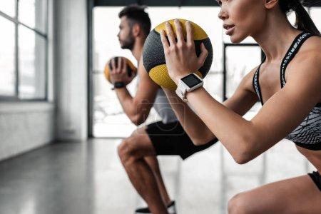 Photo pour Plan recadré de jeune couple sportif tenant des boules de médecine et s'entraînant ensemble dans la salle de gym - image libre de droit