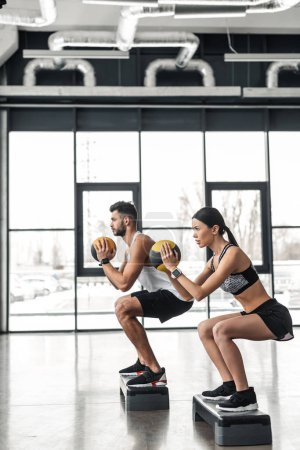 Photo for Side view of athletic young couple in sportswear training with step platforms in gym - Royalty Free Image