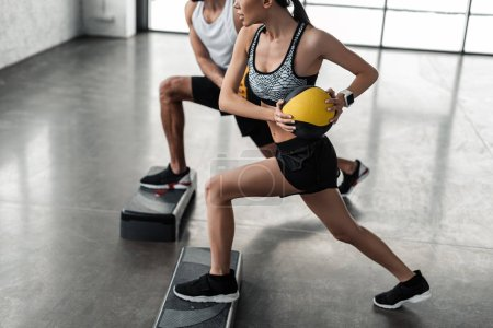 Photo for Cropped shot of sportive young couple holding medicine balls and exercising on step platforms in gym - Royalty Free Image